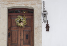 Old Wooden Door With Sandstone Lining, Wreath, Lantern And Cross On White Background