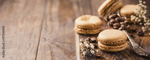 Fotobehang Macarons French coffee macarons with ganache filling with coffee beans on old wooden board on rvintage background. Holidays food concept with copy space. Banner.