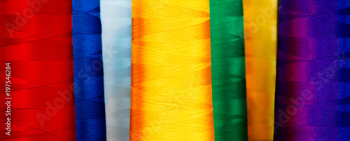 Bobbins with multicolor thread for industrial textile machines. Multicolor background
