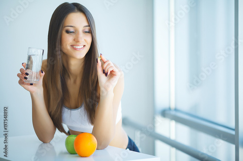 Fototapeta Beautiful Smiling Woman Taking Vitamin Pill. Dietary Supplement obraz