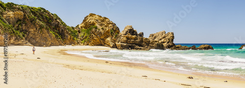Australia, New South Wales, Bermagui, Woman walking along beach