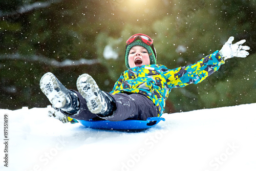 Obraz  Boy sledding in a snowy forest. Outdoor winter fun for Christmas vacation. - fototapety do salonu