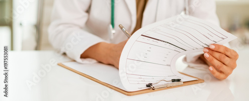 Foto  Closeup on medical doctor woman writing in clipboard