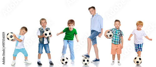 A large group of boys with soccer balls.