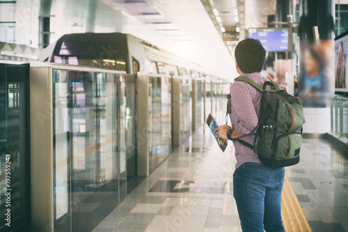 Recess Fitting Kuala Lumpur Young man traveler with backpack holding Kuala Lumpur location map in hands while looking MRT Train coming to platform in Kuala Lumpur, Malaysia.