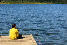 A Young Boy Sitting On A Dock And Fishing