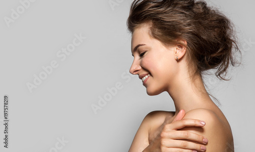 Fotografía  Beautiful woman with perfect skin and bare shoulders in profile on a gray backgr