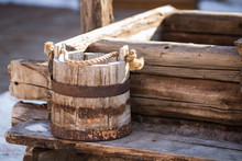 An Old Wooden Bucket Stands By The Well