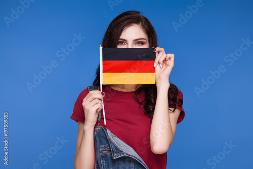 Fotomural Beautiful brunette woman holding a flag of germany in her hands and covering her mouth, on a blue background