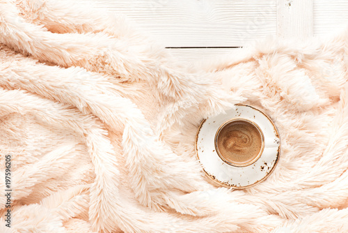 Obraz A cup of coffee on a wooden table and a warm blanket. Autumn or Winter concept, Flat lay - fototapety do salonu