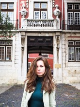 Young Woman In An Urban Street Standing Outside A Brick Building Looking At The Camera With Languishing Look