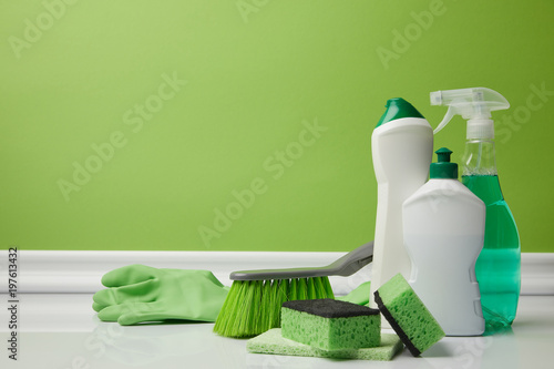 brush and domestic supplies for spring cleaning on green