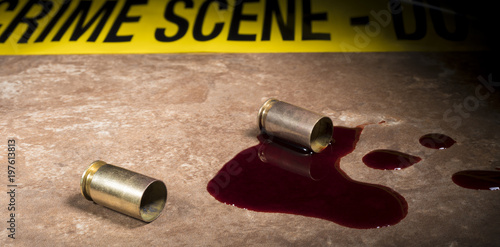 Photo Crime scene tape at the back of two spent handgun shells and blood