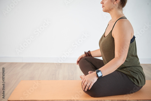 Profile view of confident young woman sitting in lotus position while having training at modern health club, copy space
