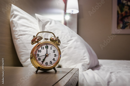 Photo alarm clock stands on a bedside table in the room or hotel room