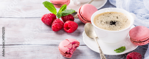 Cup of coffee with french raspberry macarons cookies on old white background. Holidays food concept, copy space. Banner.