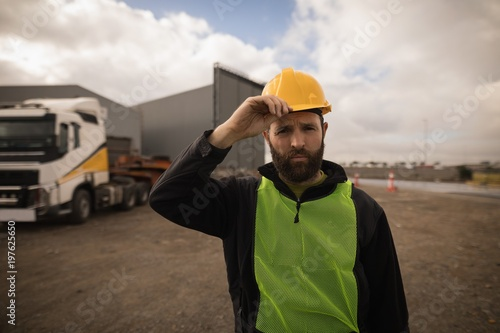 Dock worker holding his hat in shipyard