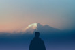 man silhouette hiker stands outdoors watching of highest mountain at sunset. concept nature and human race. copy space
