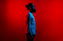 Abstract Side View Of Bearded Hipster Man In Casual With Long Hair And Wearing Eyeglasses Standing Over Red Background. Profile Portrait.
