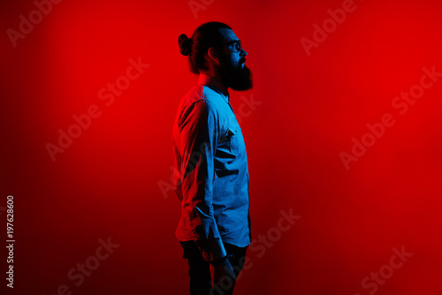 Valokuva  Abstract side view of bearded hipster man in casual with long hair and wearing eyeglasses standing over red background