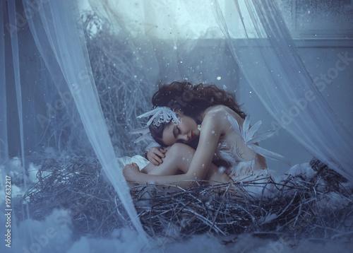 Dziewczyna siedzi w swoim gnieździe, nieśmiało pochylając głowę i obejmując nogi. Gniazdo w bajkowym domu, w pobliżu okna, z którego leje się światło, a śnieg delikatnie ślizga się. Fotografia artystyczna