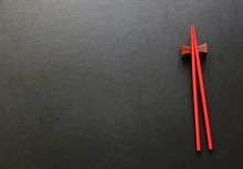 Red Wooden Chopsticks On Black Table.Copy Space,Flat Lay