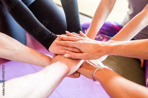 Fototapety, obrazy: Friendly sports team folded their hands in a circle sitting in the gym