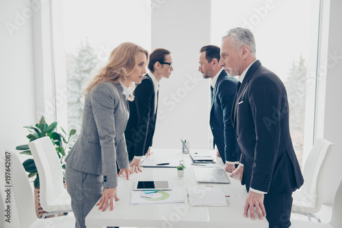 Foto Business competition, four stylish business persons in suits having disagreement