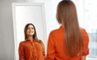 wardrobe, fashion, style and people concept - happy woman in orange shirt looking at mirror reflection at home or clothing store dressing room