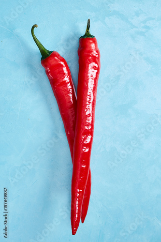 Staande foto Hot chili peppers Fresh red hot pepper on a blue background, top view, close-up