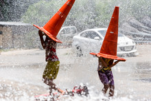 Children Play With Water Sprinkler In The Summer. Song Kran Festival Concept