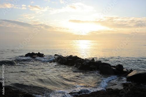 Foto  traumhafte Lichtstimmung bei Sonnenaufgang an einer malerischen Buhne am Meer