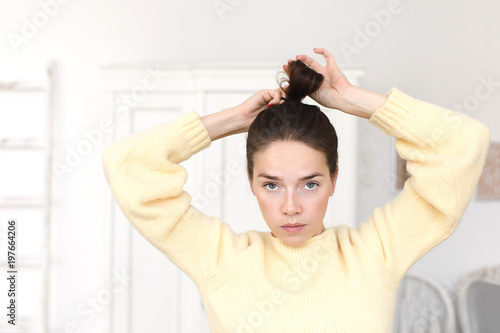 Serious emotionless woman in sweater looking at camera while setting hair in ponytail Slika na platnu