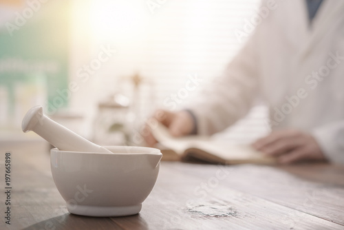 Tuinposter Apotheek Pharmacist grinding a preparation using a pestle
