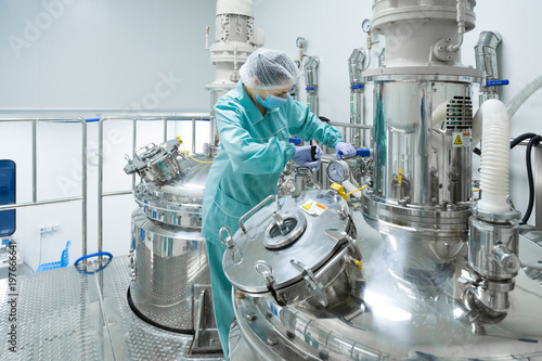 Photo  Pharmaceutical factory woman worker in protective clothing operating production
