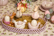 Easter Decorative Composition On A Vintage Background. Spring. A Flowerpot With Muscari Flowers, A Porcelain Rabbits, Eggs In The Hay.