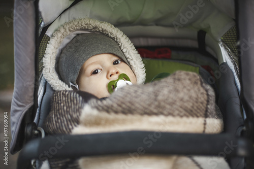 Portrait of cute toddler with pacifier in mouth lying on baby stroller at park during autumn