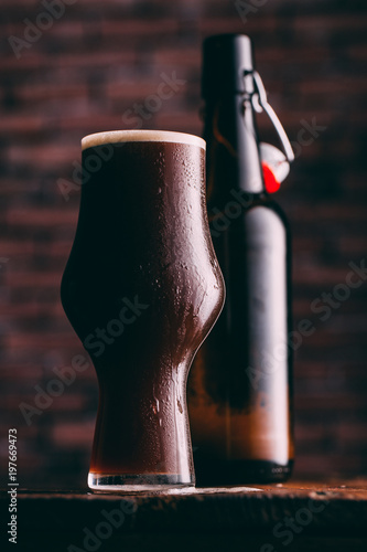Tuinposter Bier / Cider Stout beer in glass abd bottle on dark background