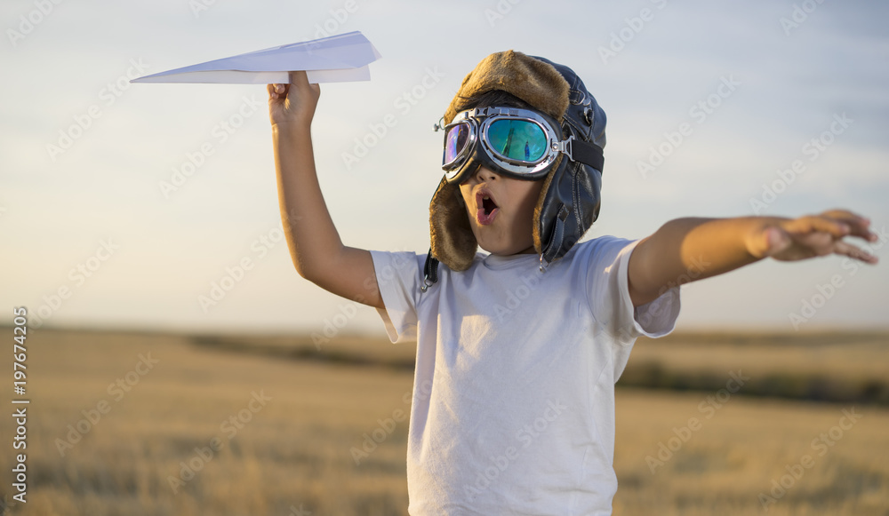 Fototapety, obrazy: Fun Little boy wearing helmet and dreams of becoming an aviator while playing a paper plane at sunset