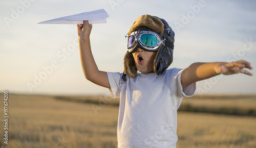 Tableau sur Toile Fun Little boy wearing helmet and dreams of becoming an aviator while playing a