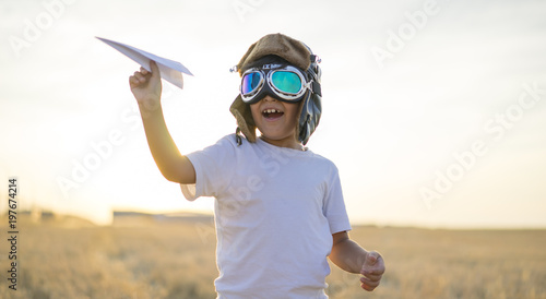 Leinwand Poster Kid, Little boy wearing helmet and dreams of becoming an aviator while playing a