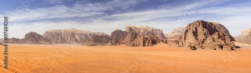 Foto auf Gartenposter Wuste Sandig panoramic view to red sand desert with mountains rocks in Jordan
