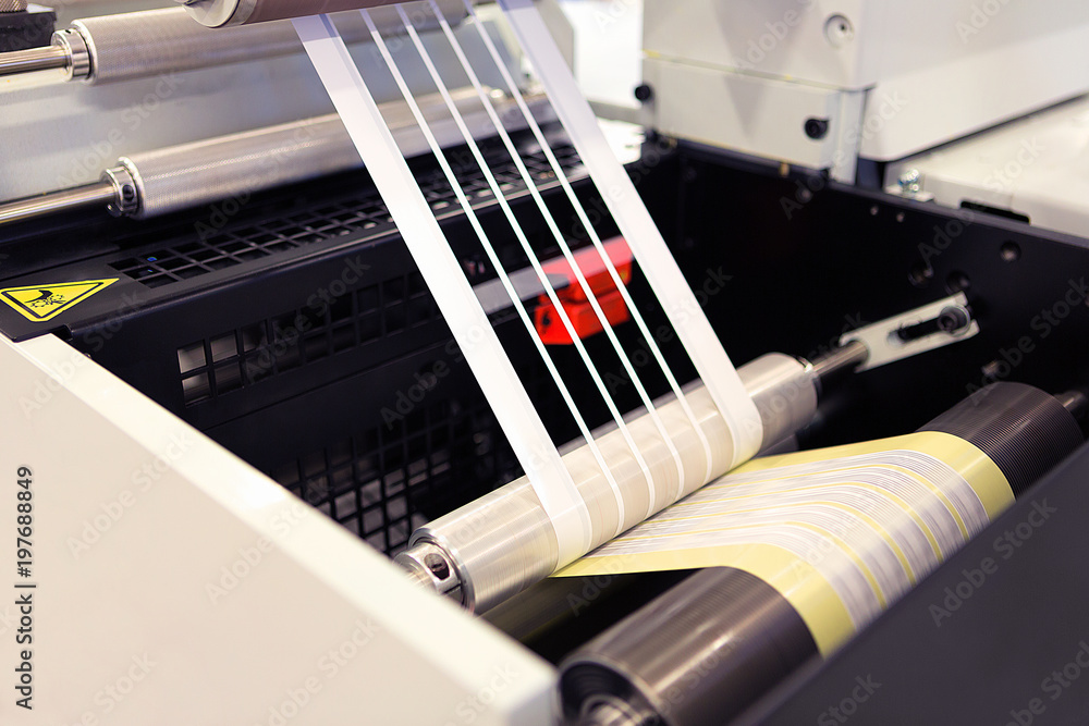 Fototapeta Close-up shot of labels manufacturing on flexo printing machine. Photo detail of matrix waste or trim removal from adhesive material on flexographic press.