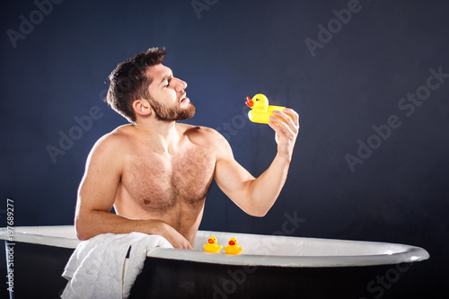 Cadres-photo bureau Akt Handsome naked muscular adult happy man taking bath and playing with toy ducks, on dark-blue background