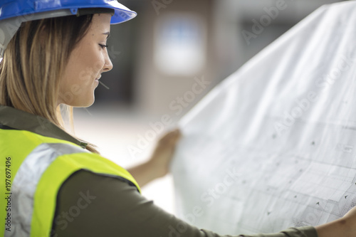 Woman wearing hard hat looking at construction plan