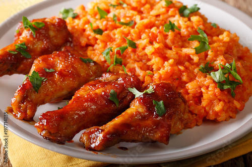 Nigerian food: spicy Jollof rice with fried chicken closeup. horizontal