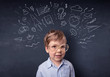 Little boy in front of a drawn up blackboard