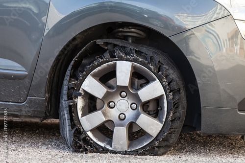 Photo Destroyed blown out tire with exploded, shredded and damaged rubber on a modern suv automobile