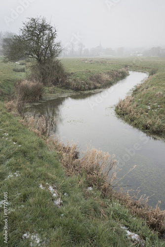 Spoed Foto op Canvas Khaki Cold misty Winter landscape over stream in English countryside