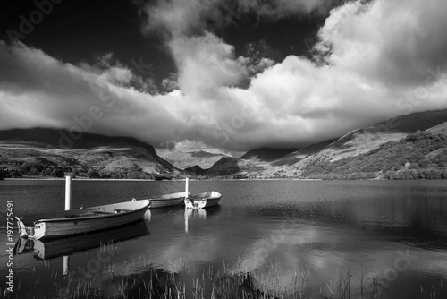 Staande foto Bleke violet Black and white Landscape image of rowing boats on Llyn Nantlle in Snowdonia at sunset